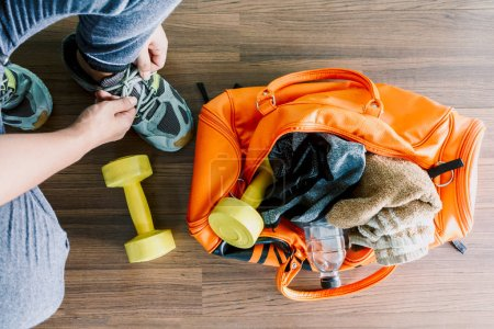 Photo for Man tying her shoelaces with bag and fitness equipment - Royalty Free Image