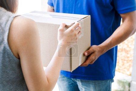 Photo pour Femme acceptant une boîte de livraison du livreur - image libre de droit