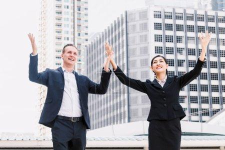 Photo pour Des gens d'affaires prospères fêtent avec les bras levés - image libre de droit