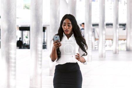 Photo pour Femme africaine avec café et smartphone - image libre de droit