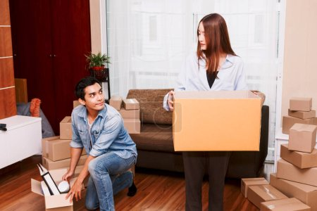 Photo for Happy couple packing boxes and moving into new home.Moving house - Royalty Free Image