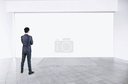 Photo for Businessman in black suit standing in empty interior with mock up white space - Royalty Free Image