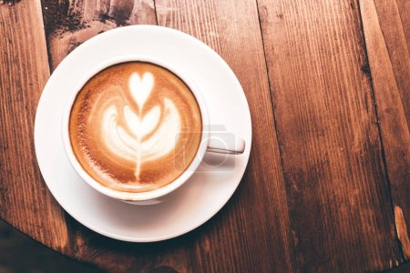 Photo for Coffee latte art on wooden table in coffee shop - Royalty Free Image