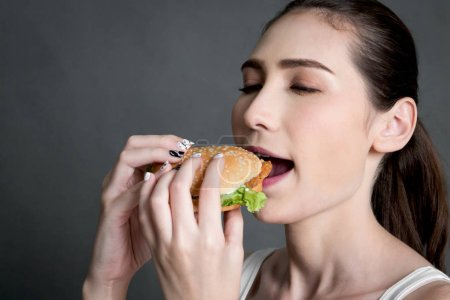 Photo for Young woman eating hamburger on gray background. Junk food and fast food concept - Royalty Free Image