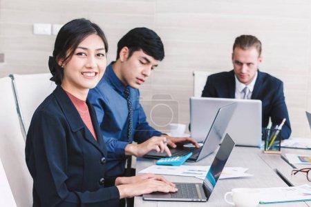 Photo pour Gens d'affaires à l'aide d'ordinateurs portables et de discuter ensemble dans la salle de réunion. Concept de travail d'équipe - image libre de droit