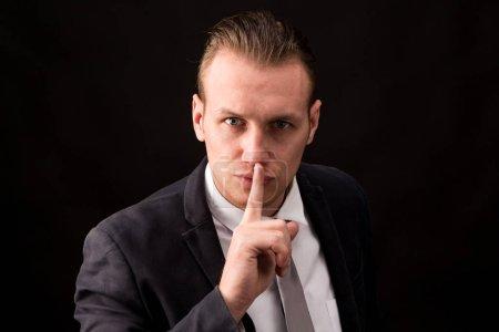 Photo pour Geste calme homme d'affaires avec le doigt sur fond noir - image libre de droit