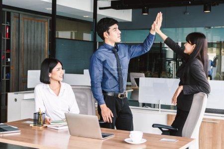 Photo pour Équipe d'affaires réussie faisant un geste de cinq fois au bureau - image libre de droit