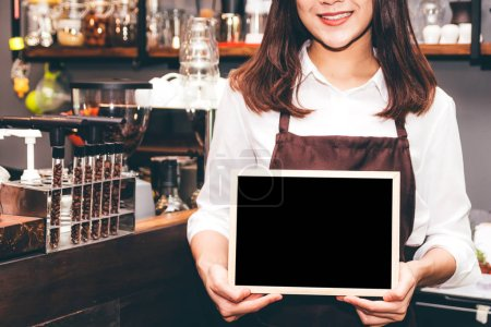 Photo for Barista holding chalkboard  in coffee shop restaurant - Royalty Free Image