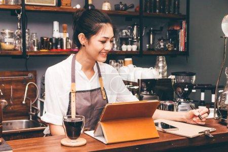 Photo pour Femme de barista à l'aide de tablette numérique calcul en bar comptoir café - image libre de droit