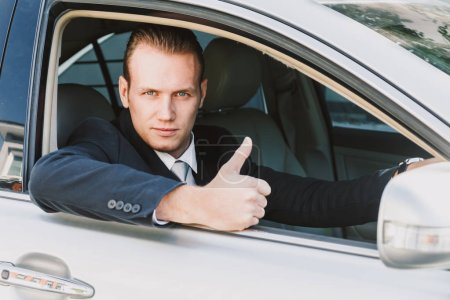Photo pour Bel homme d'affaires en costume dans une voiture - image libre de droit