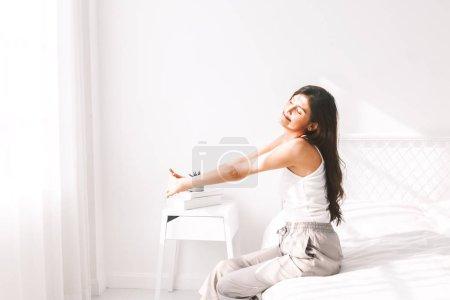 Foto de Mujer que estira en la cama después de despertar hasta - Imagen libre de derechos