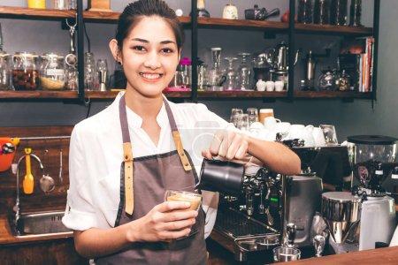 Photo pour Barista tenant du lait pour faire café latte art dans un café - image libre de droit
