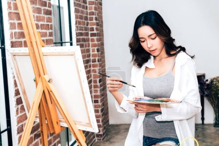 Photo for Young woman artist drawing on canvas with color palette and watercolor paints at home - Royalty Free Image