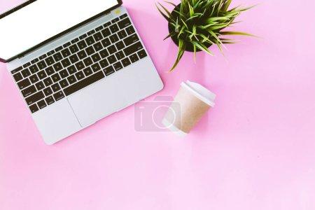 Photo pour Vue de dessus du portable ordinateur et tasse café sur fond rose. Poser de plat - image libre de droit