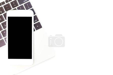 Photo pour Vue de dessus du portable et smartphone avec écrans vides sur la table de bureau blanc bureau. Poser de plat - image libre de droit