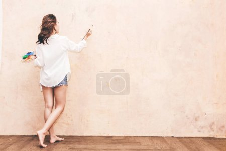 Photo for Young woman artist drawing on wall with copy space and paintbrush and watercolor paints at home - Royalty Free Image