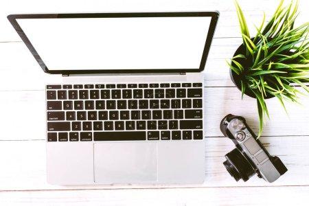 Photo pour Vue de dessus d'ordinateur portable avec écran vide sur la table de bureau en bois blanc bureau. Poser de plat - image libre de droit