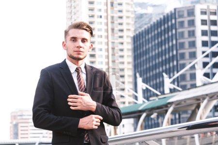 Photo pour Portrait de bel homme en costume noir permanent à l'extérieur - image libre de droit