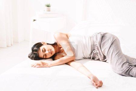 Photo pour Femme, dormir et se sentir à l'aise sur le lit blanc dans la chambre de détente - image libre de droit