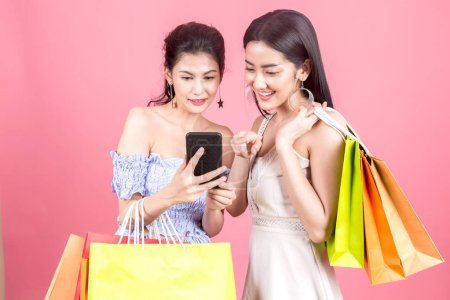 Photo for Portrait of two beautiful women holding shopping bags and enjoying shopping on pink background - Royalty Free Image