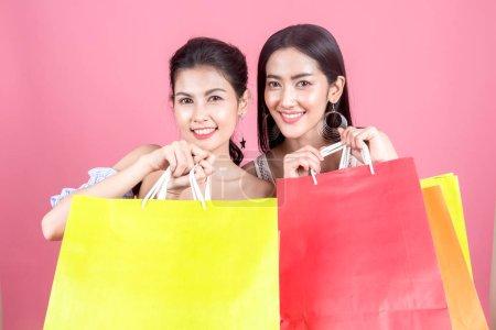 Photo pour Portrait de deux belles femmes tenant des sacs à provisions et appréciant shopping sur fond rose - image libre de droit