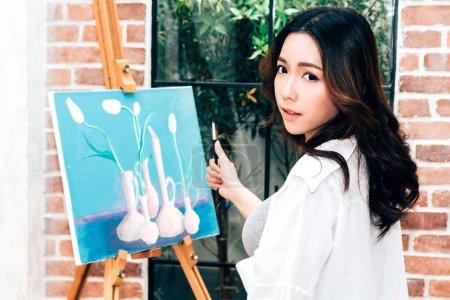 Photo pour Jeune femme artiste dessin sur toile avec palette et aquarelle peintures de couleur à la maison - image libre de droit