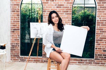 Photo pour Jeune femme artiste posant avec toile vide à la maison - image libre de droit