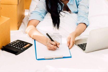 Photo pour Jeune femme travaillant et liste de contrôle d'un carton boîte sur lit à la maison - affaires en ligne et le concept de la livraison - image libre de droit