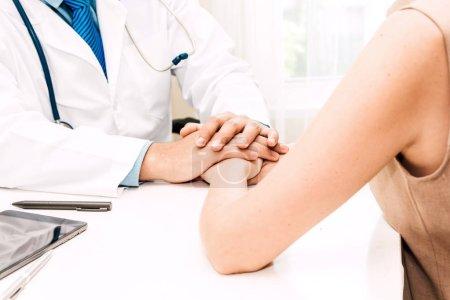Photo pour Docteur consulting et tenant patiente main rassurante avec soin sur table de médecins en médecine et hospital.healthcare - image libre de droit