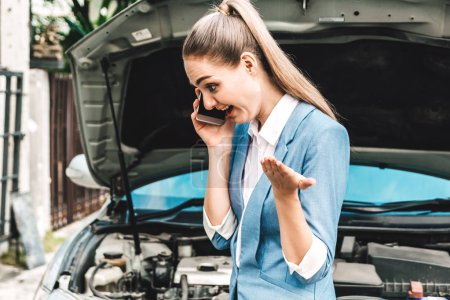 Photo for Woman calling for assistance with broken down car engine on street - Royalty Free Image