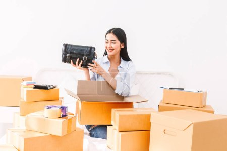 Photo pour Pigiste de la jeune femme travail PME affaires achats en ligne et emballage femme sac avec boîte en carton sur lit à la maison - concept d'expédition et de livraison en ligne entreprise - image libre de droit