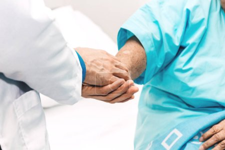 Photo for Doctor holding elderly person patient hand with care and consulting in hospital.healthcare and medicine - Royalty Free Image