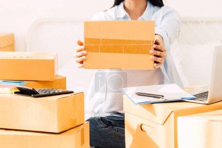 Photo pour Pigiste de la jeune femme travaille et la tenue de carton boîte sur lit à la maison - concept en ligne et livraison d'entreprise PME - image libre de droit