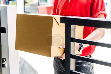 Photo for Delivery man with cardboard  box near house of customer - Royalty Free Image