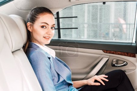 Photo for Businesswoman in back seat of luxury car - Royalty Free Image