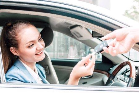 Geschäftsfrau zeigt Autoschlüssel, während sie im Auto sitzt