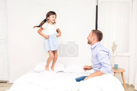 Photo for Father with little daughter having fun and playing together on the bed at home.Love of family and father day concept - Royalty Free Image