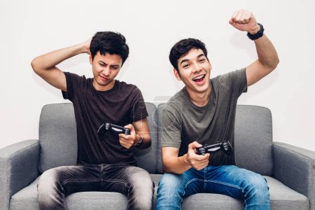 Photo for Two friends sitting on sofa and enjoying play video game together at home - Royalty Free Image