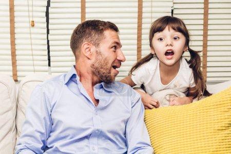 Foto de Padre con hija pequeña diversión y jugar juntos en el sofá en casa. Amor de familia y padre concepto de día - Imagen libre de derechos
