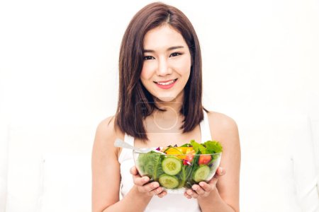 Photo for Happy woman eating and showing healthy fresh salad in a bowl.dieting concept.healthy lifestyle with green food - Royalty Free Image