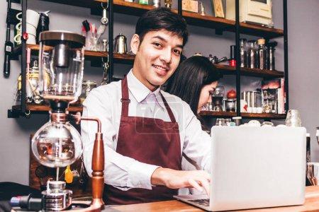Photo pour Portrait de la propriétaire de petite entreprise du couple souriant et travail avec ordinateur portable derrière le bar comptoir dans un café. Barista de couple à l'aide de machine à café pour préparer du café au café - image libre de droit