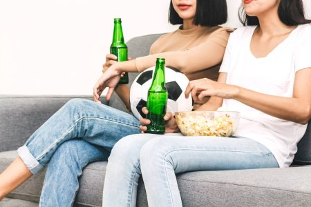 Photo for Two woman friends eating popcorn and drinking beer together and watching soccer game on sofa at home.Friendship and party concept - Royalty Free Image