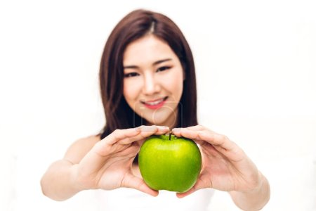 Photo for Woman holding and eating fresh green apple on white background.dieting concept.healthy lifestyle - Royalty Free Image