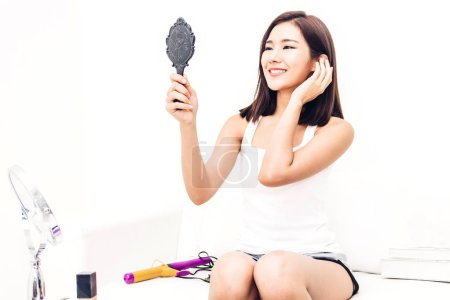 Photo for Smiling young beautiful asian woman fresh healthy skin looking on mirror at home.facial beauty and cosmetic concept - Royalty Free Image