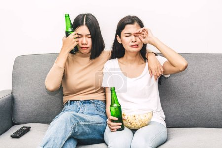 Photo for Two woman friends eating popcorn and drinking beer together and watching television on sofa at home.Friendship and party concept - Royalty Free Image