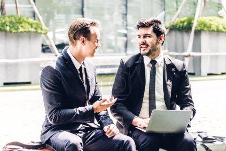 Photo pour Deux partenaires d'affaires image en noir élégant costume parler et travailler ensemble tout en discutant de nouvelle stratégie avec l'ordinateur portable à la ville. Affaires et démarrage idée concept - image libre de droit