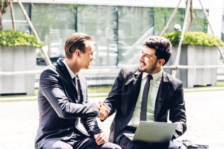 Photo for Image two business partners in black elegant suit successful handshake and talking together while discussing new strategy with laptop computer at city.Business and startup idea concept - Royalty Free Image