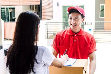 Photo pour Femme mettant la signature dans le presse-papiers sur la boîte en carton avec la notion de service livraison man.courier - image libre de droit