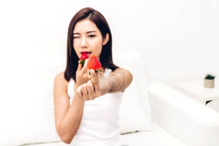 Photo for Woman eating fresh strawberry on sofa at home.dieting concept.healthy lifestyle - Royalty Free Image