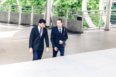 Photo for Two smiling businessman coworkers in black suit talking and walking.business people discussing strategy in the modern city - Royalty Free Image